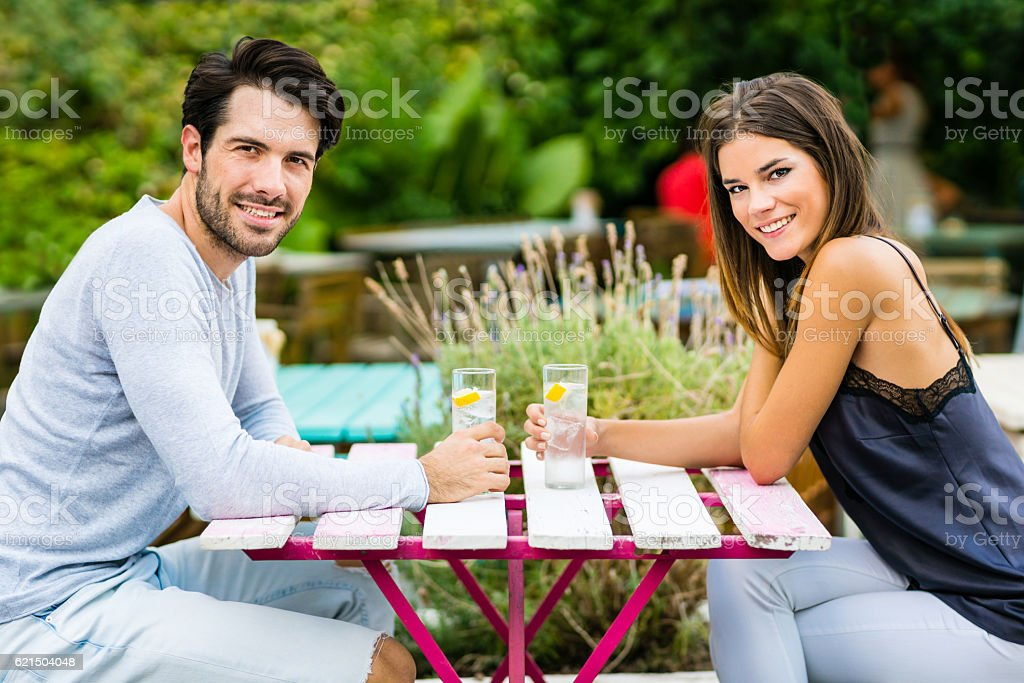 Young couple having conversation at outdoor bar stock photo