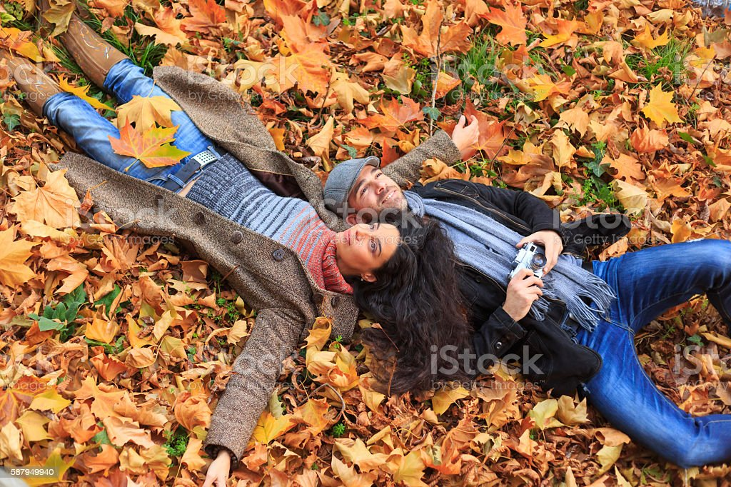 Young couple having fun and lying down on leaves stock photo