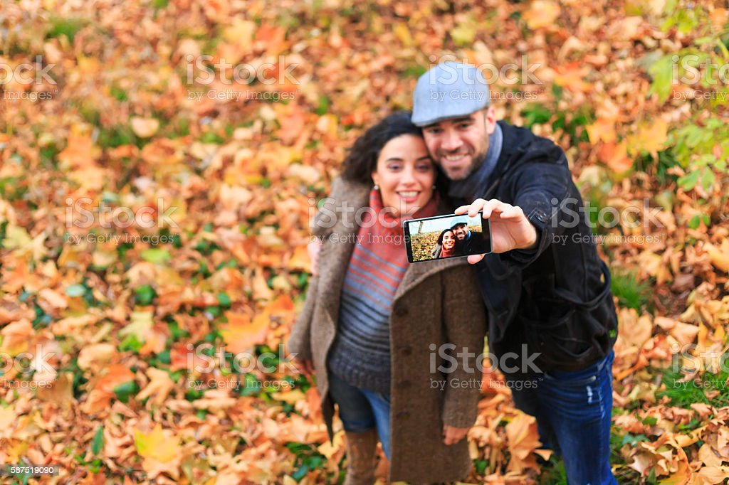 Young couple having fun and making selfie in park stock photo