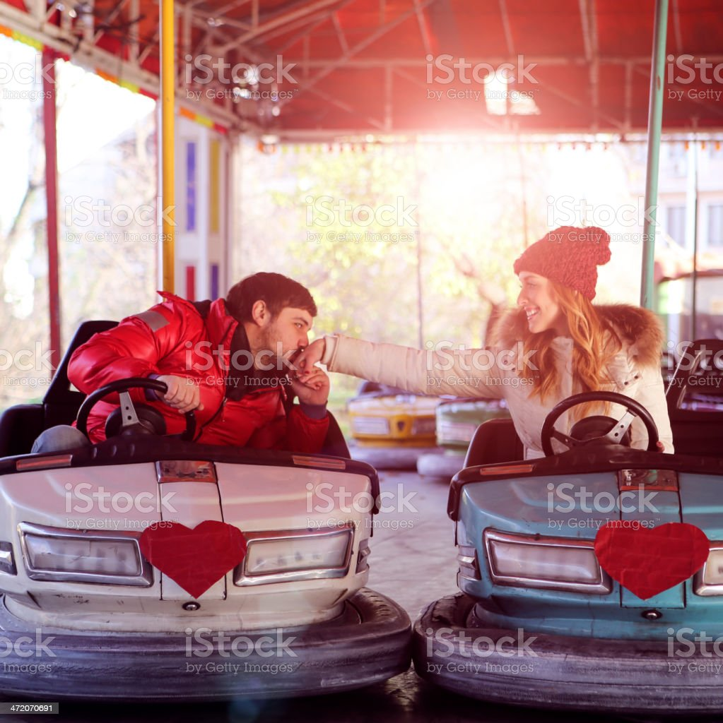 Young Couple Having Fun Driving Bumper Cars. stock photo