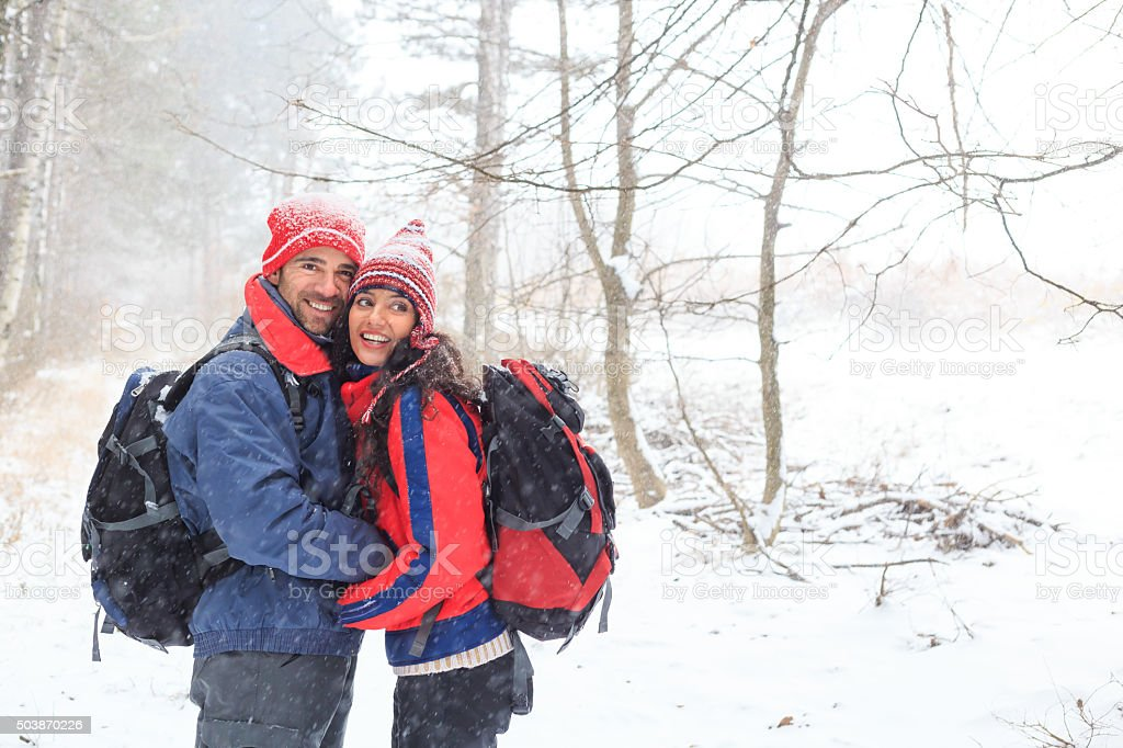 Young couple having fun in the snow forest stock photo