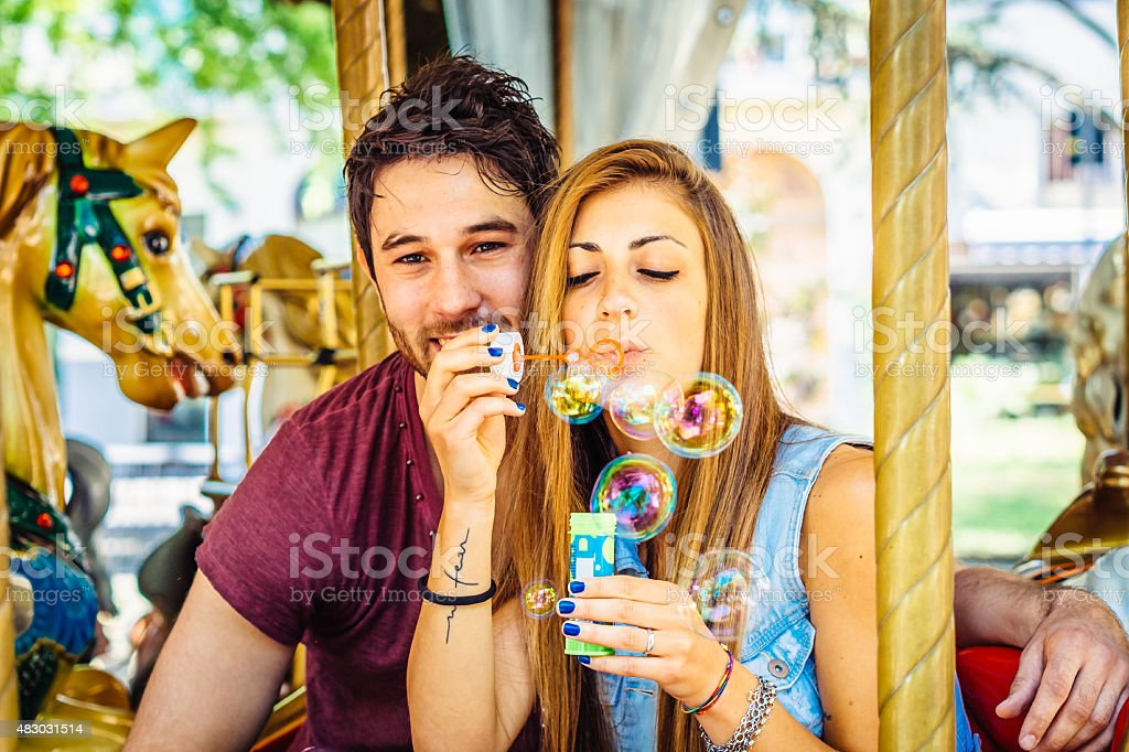 Young Couple Having Fun On Merry Go Round stock photo