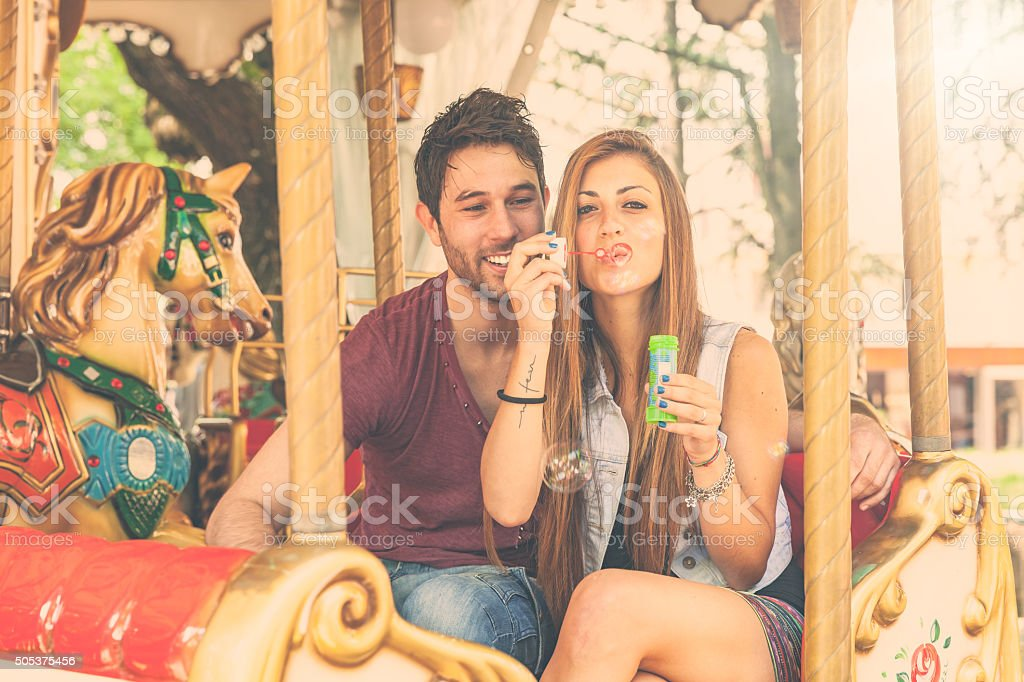 Young couple having fun on Merry-Go-Round stock photo