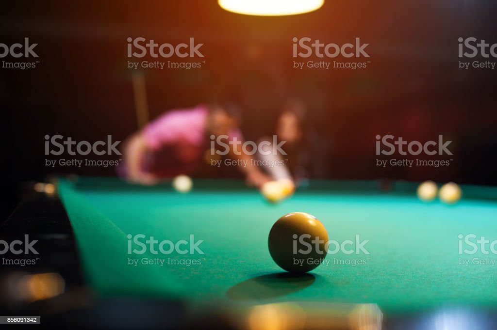 Playing billiard background - young couple having fun playing snooker.