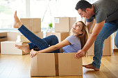 Young couple having fun while they moving into new home