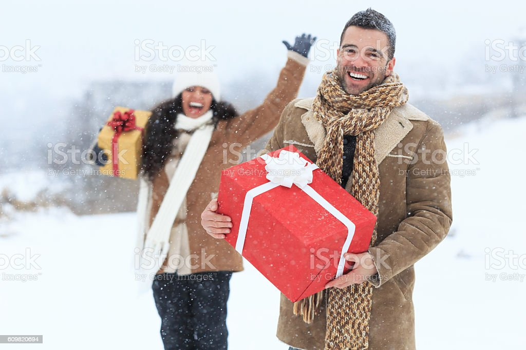 Young couple having fun with christmas presents on snow mountain stock photo