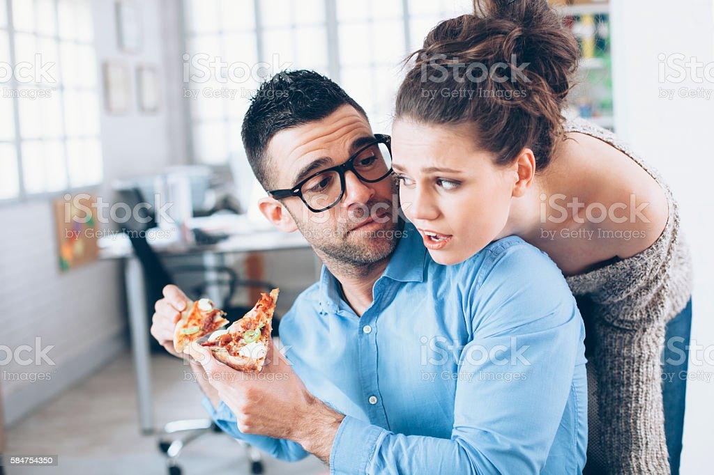 Young couple having pizza lunch break at workplace stock photo