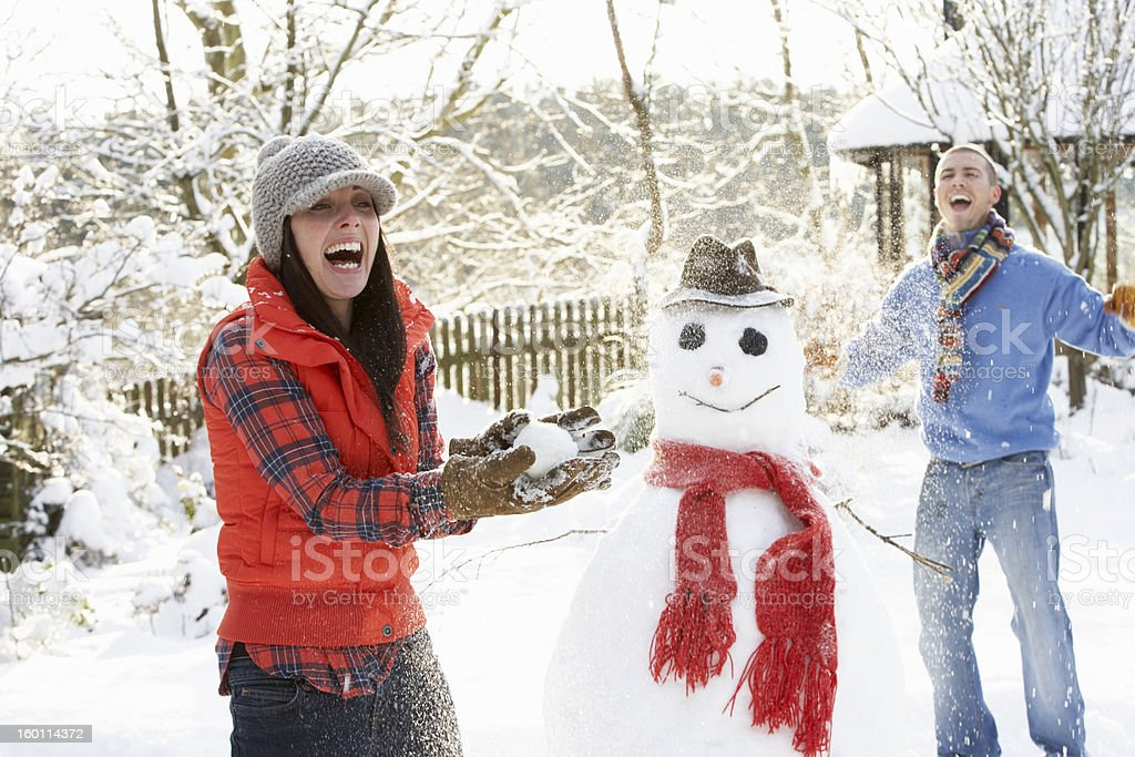 Young Couple Having Snowball Fight In Garden stock photo