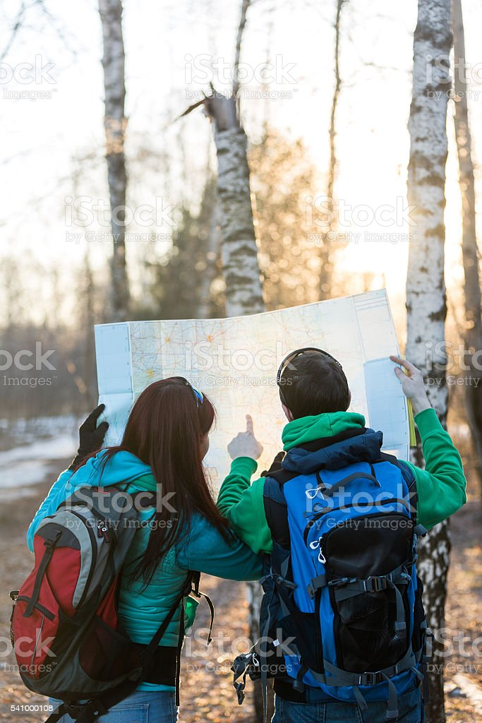 Young couple hikers looking at map. stock photo