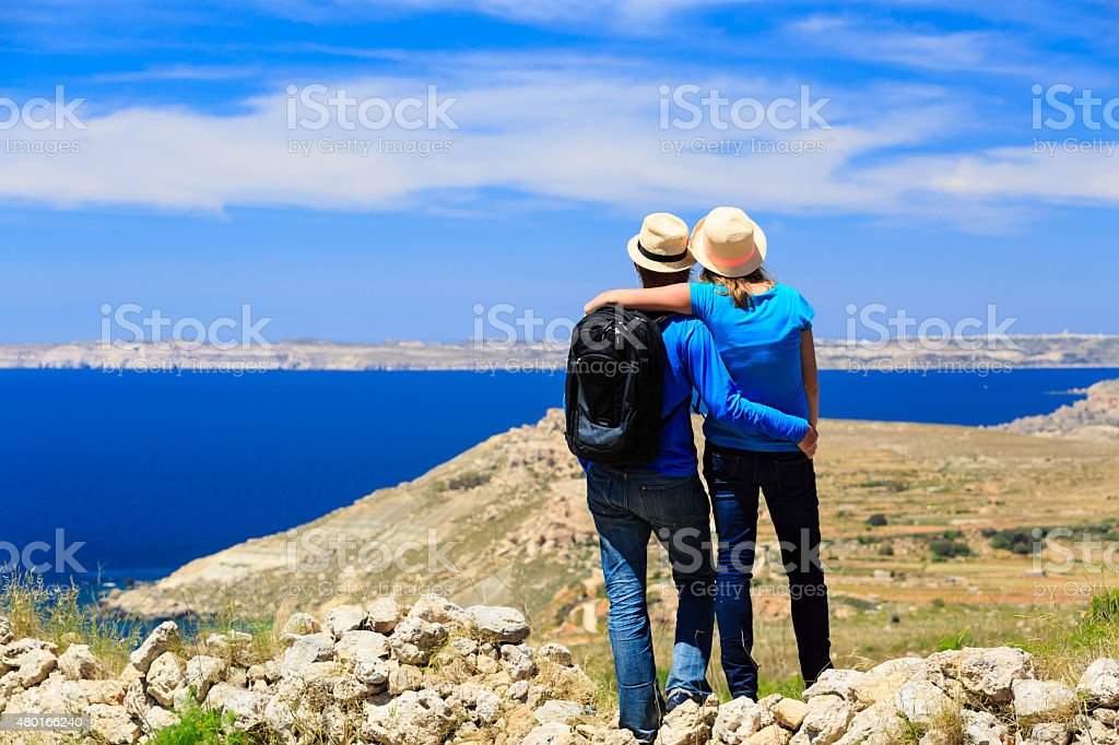 young couple hiking in mountains looking at scenic view stock photo