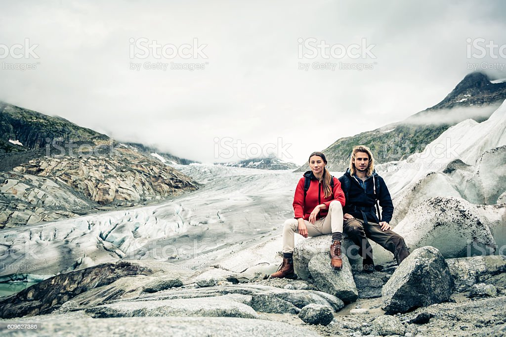 Young Couple Hiking in the Swiss Alps, Taking a Break stock photo