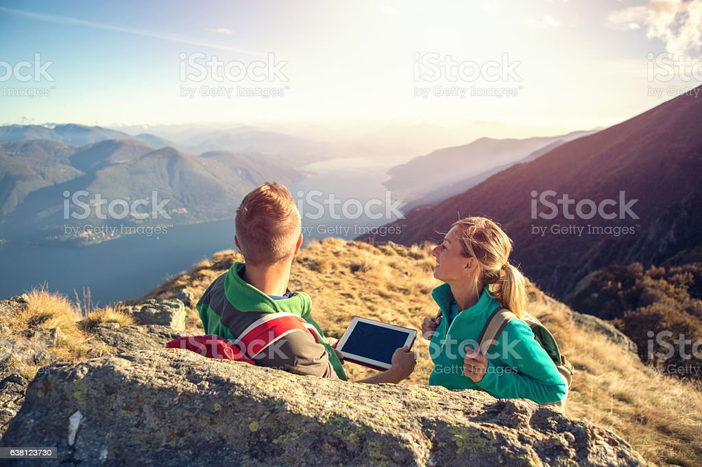 Young couple hiking look at digital map on tablet stock photo