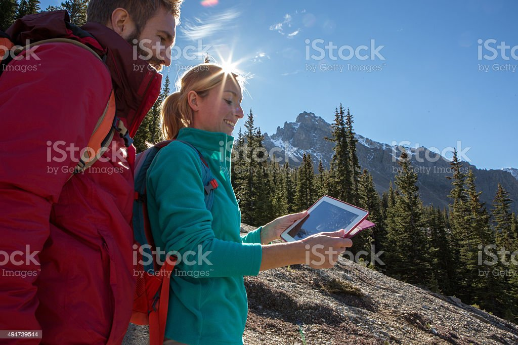 Young couple hiking looks at digital map stock photo