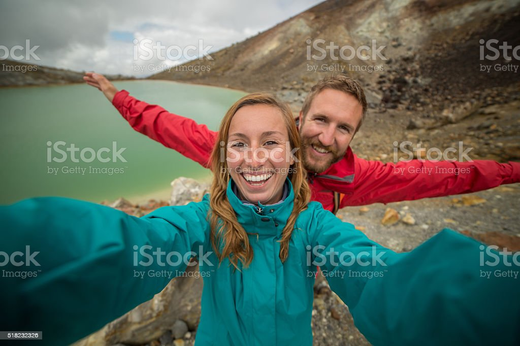 Young couple hiking on Tongariro Alpine Crossing take selfie portrait stock photo