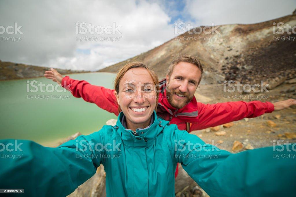 Young couple hiking on Tongariro Alpine Crossing take selfie portrait stock photo