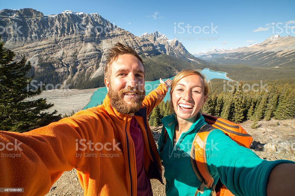 Young couple hiking reaches view point and takes selfie portrait stock photo