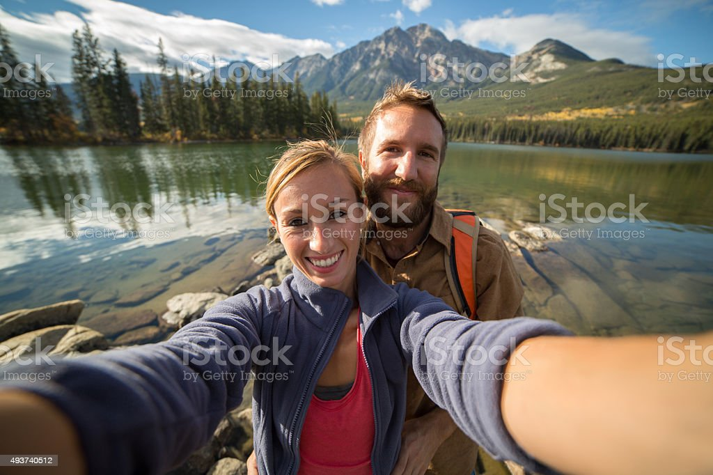 Young couple hiking takes a selfie portrait by the lake stock photo