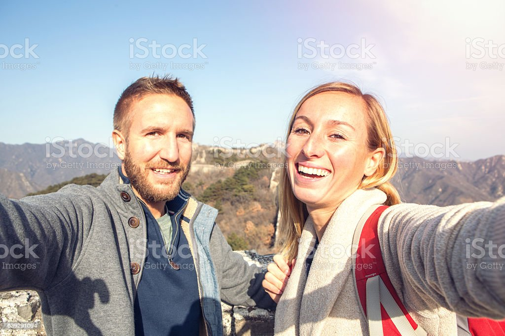 Young couple hiking the Great Wall of China taking selfie stock photo