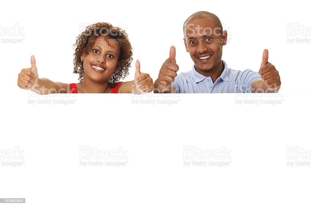 Young couple holding a blank placard. Thumbs up. stock photo
