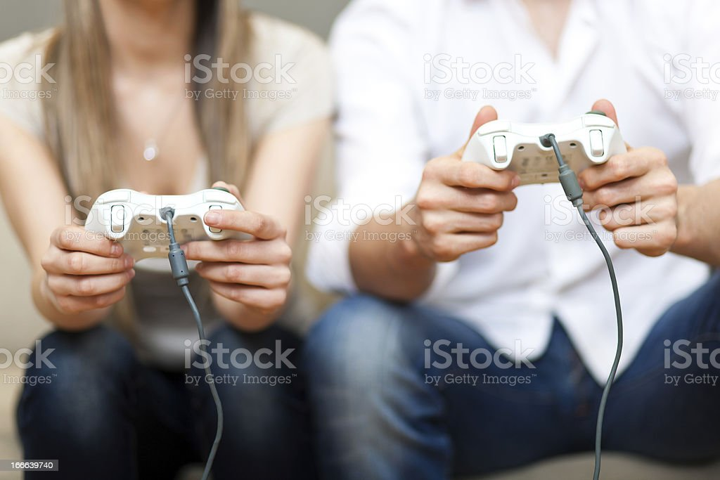 A young couple holding a joystick while playing a video game stock photo