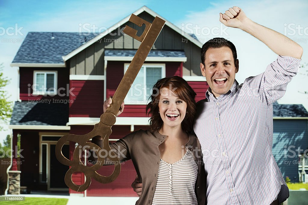 Young couple holding a large key royalty-free stock photo
