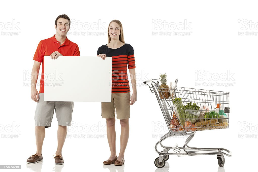 Young couple holding a placard by shopping cart royalty-free stock photo