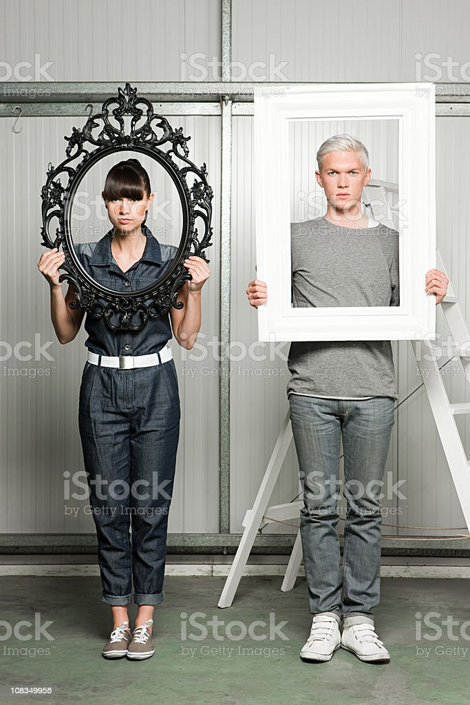 Young couple holding black and white picture frames royalty-free stock photo