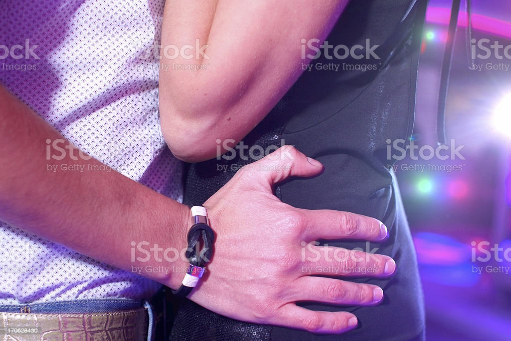 A young couple holding each other at a disco royalty-free stock photo