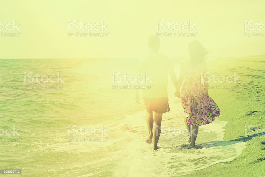 Young couple holding hands and walking on the beach stock photo