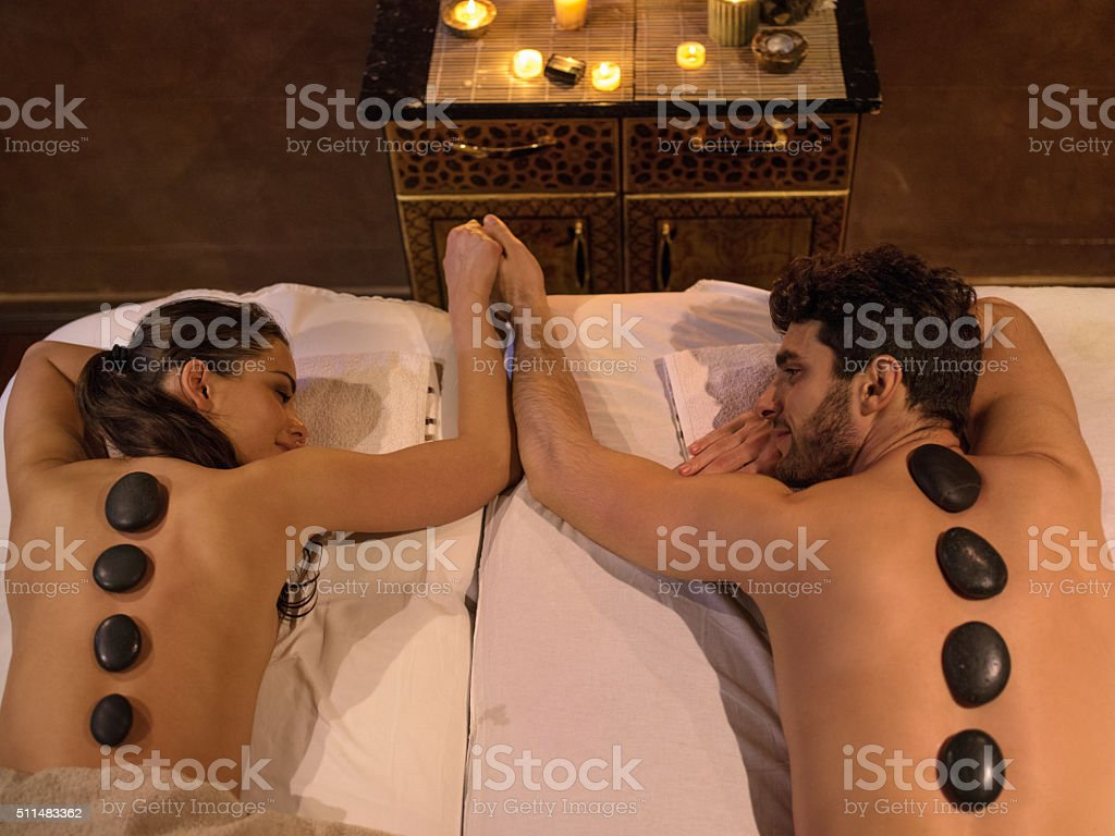 Young couple holding hands during lastone therapy at the spa. stock photo