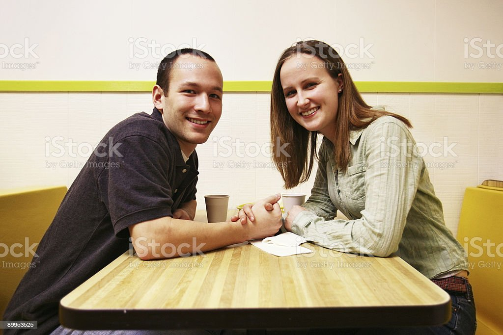 Young Couple Holding Hands in a Donut Shop royalty-free stock photo