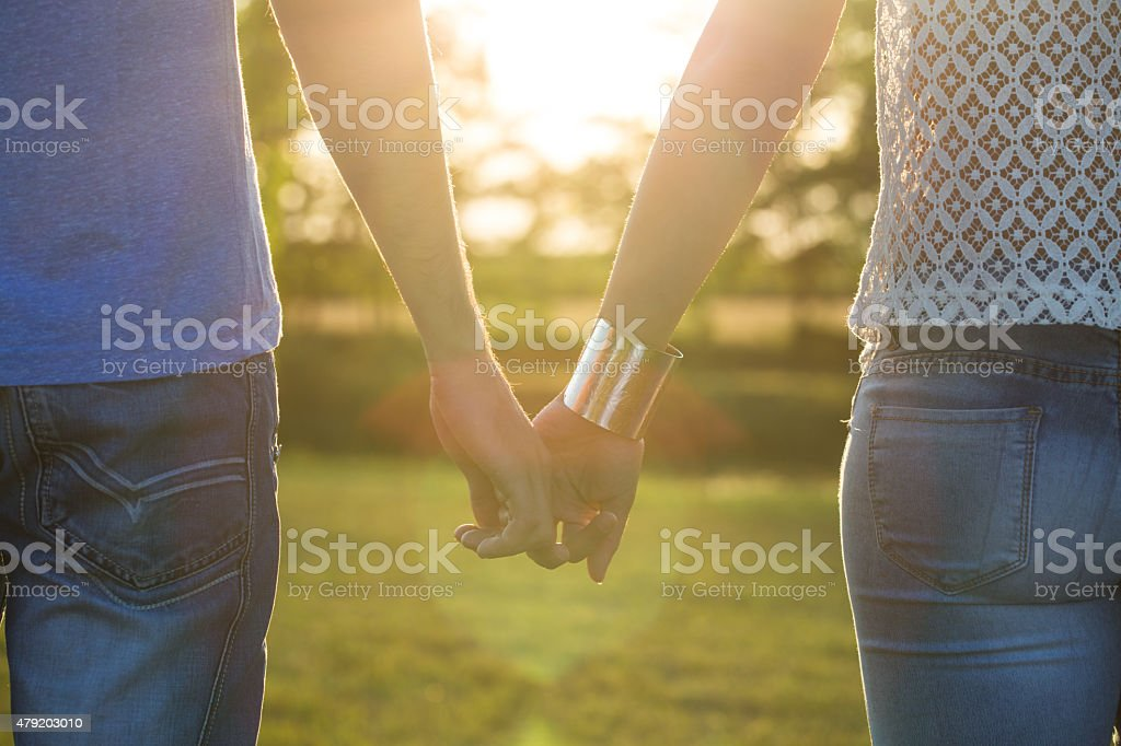 young couple holding hands in sunset stock photo