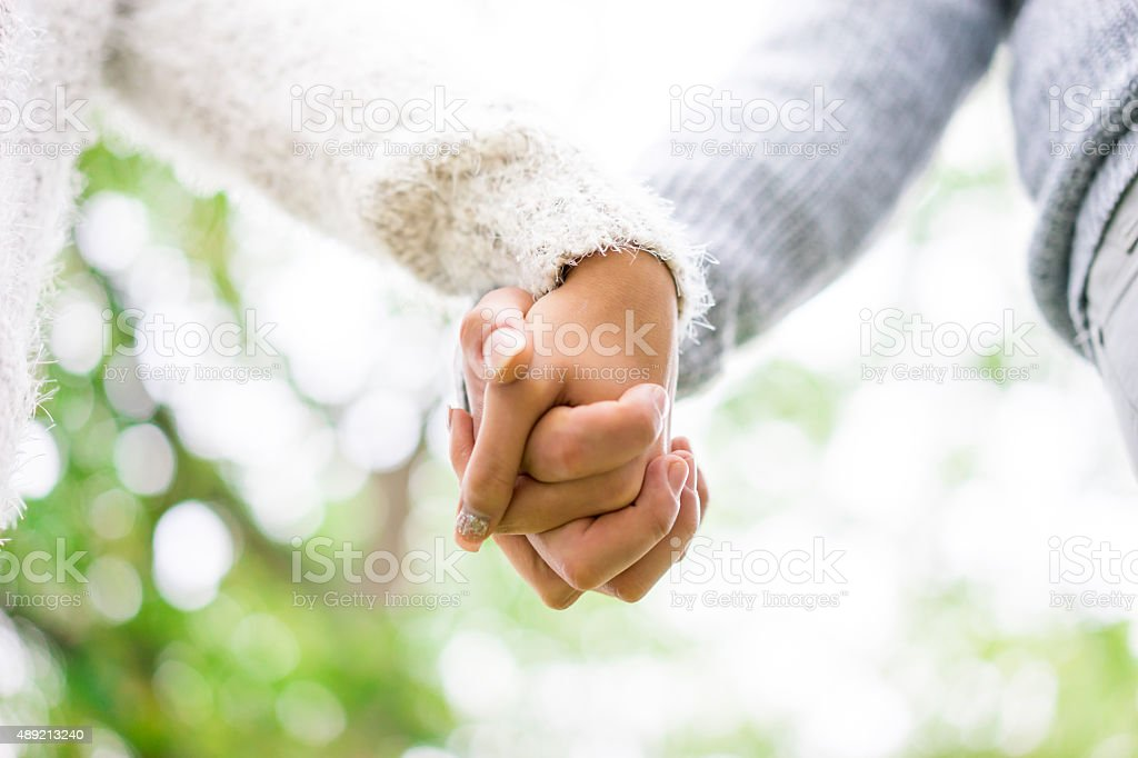young couple holding hands in the park, London. stock photo