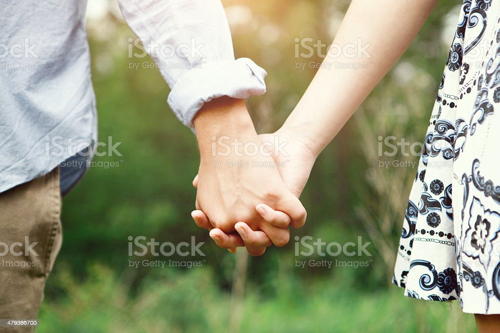 Young Couple Holding Hands Outside stock photo