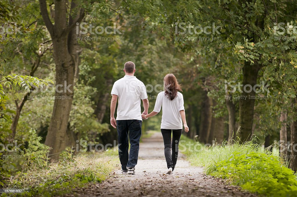 Young couple holding hands while walking on park path royalty-free stock photo