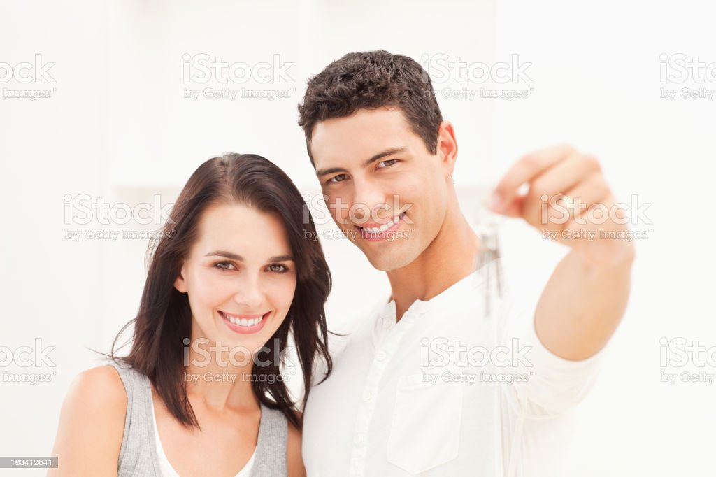 Young Couple Holding Out New House Keys stock photo