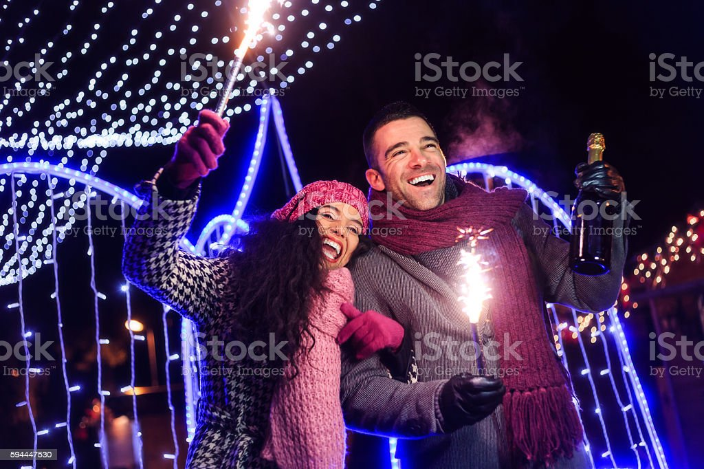 Young couple holding sparkling candles and champagne outdoors stock photo