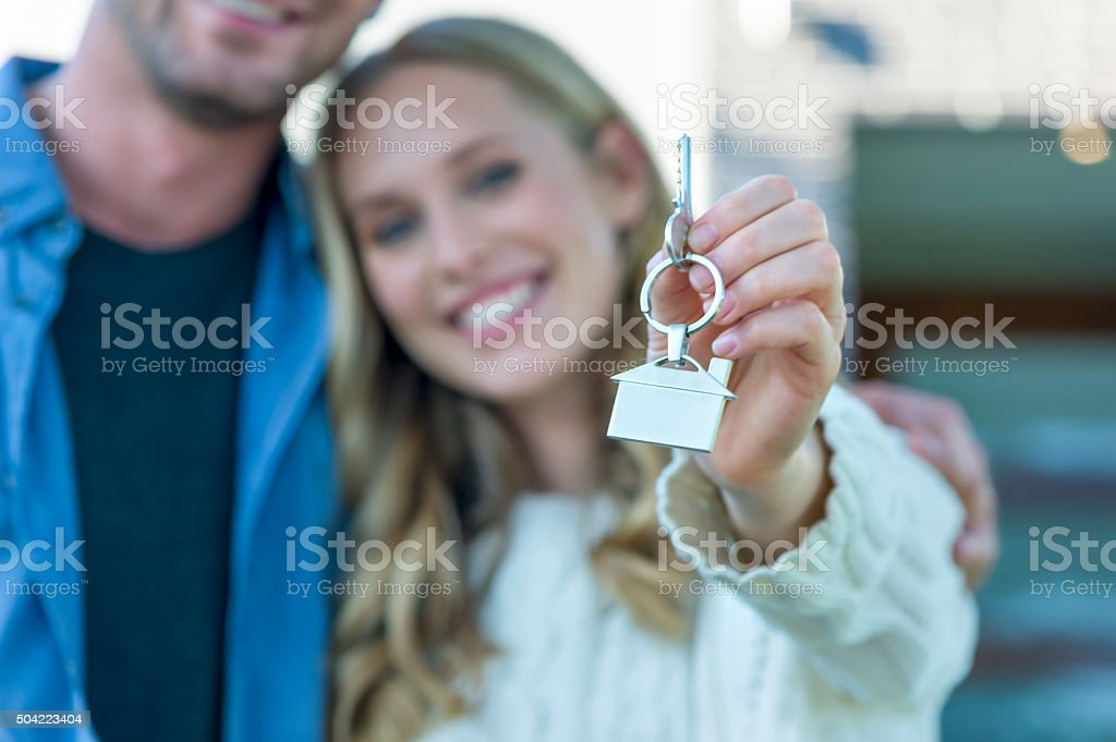 Young couple holding their new house key. stock photo