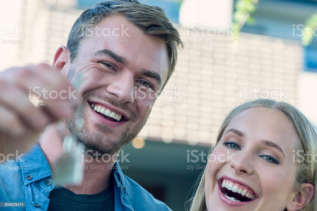 Young couple holding their new house key stock photo
