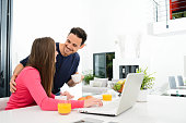 young couple home with laptop computer having coffee in kitchen
