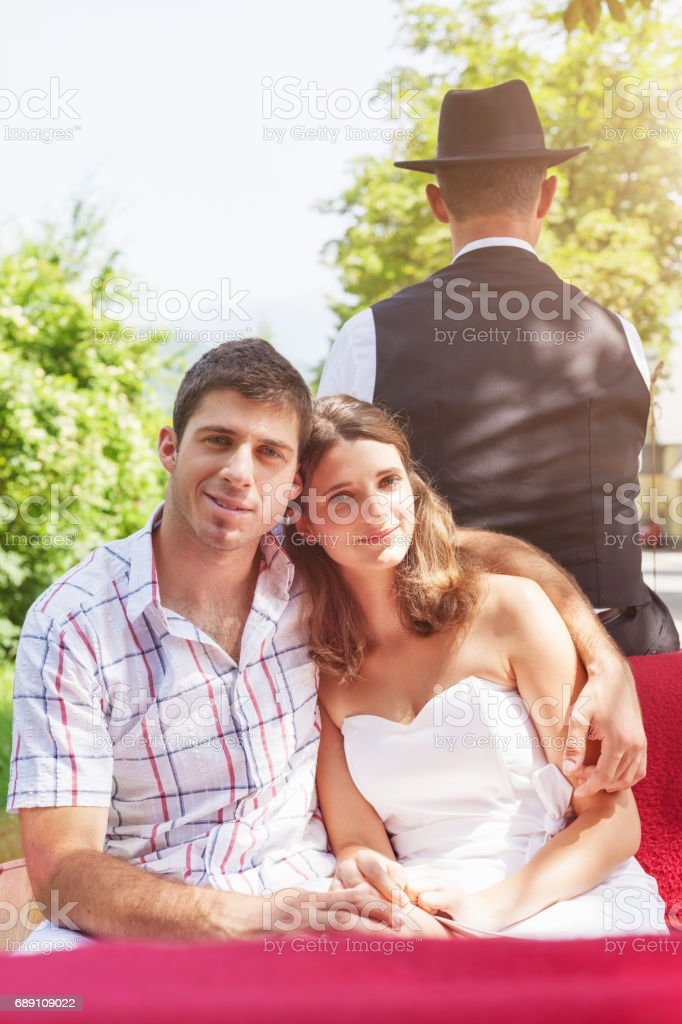 Young couple horsedrawn carriage ride in summer stock photo