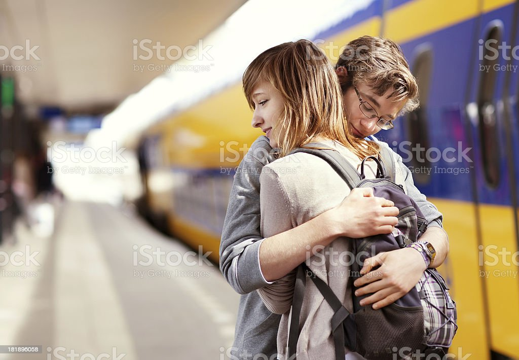 young couple hugging against  train at the background stock photo