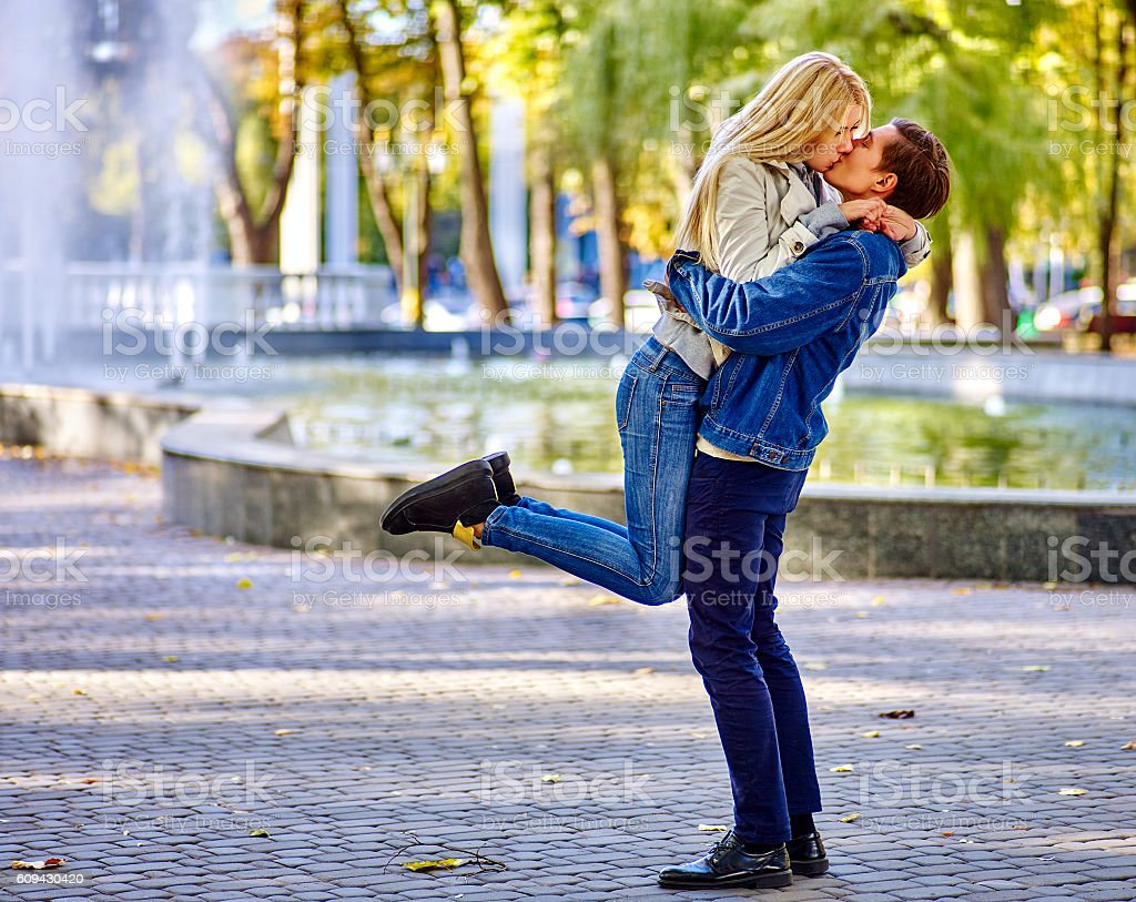 Young couple hugging and kissing in park. stock photo
