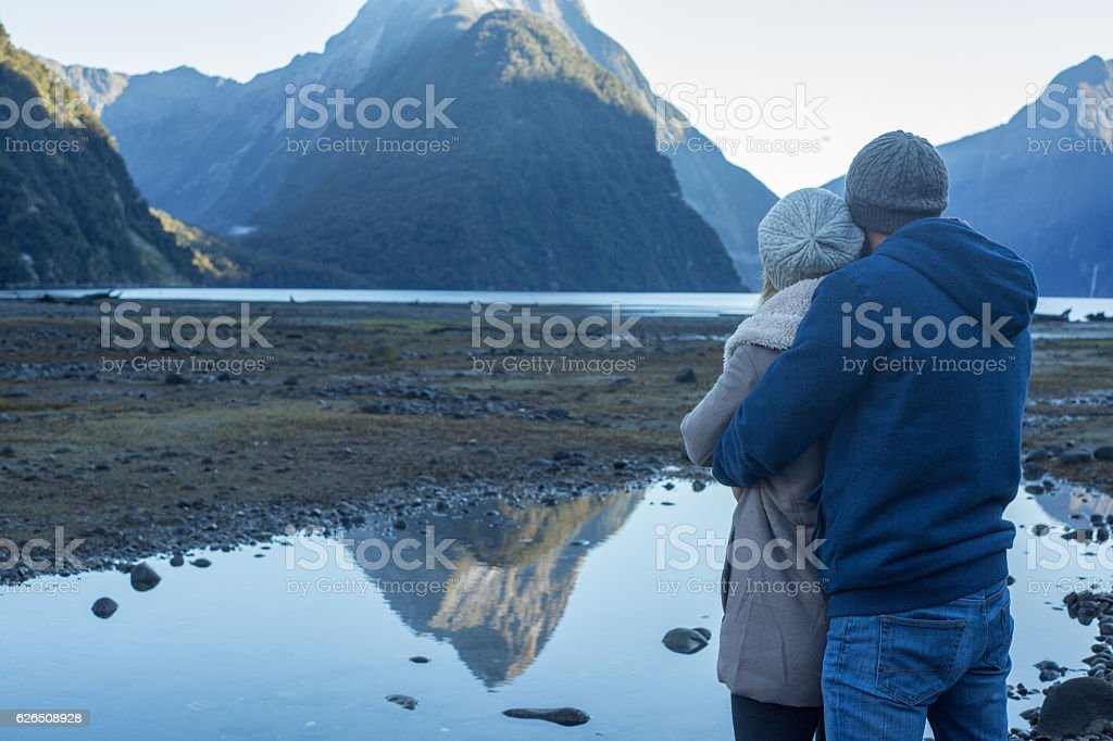 Young couple hugging and looking at spectacular landscape stock photo