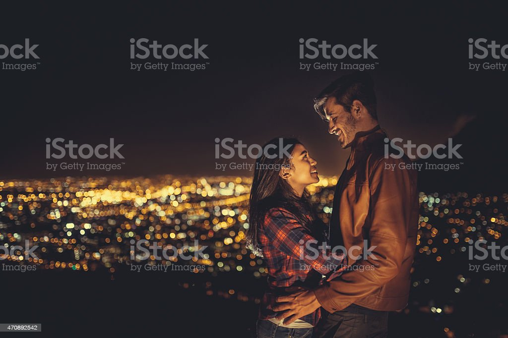 Young couple hugging at night with the city behind stock photo