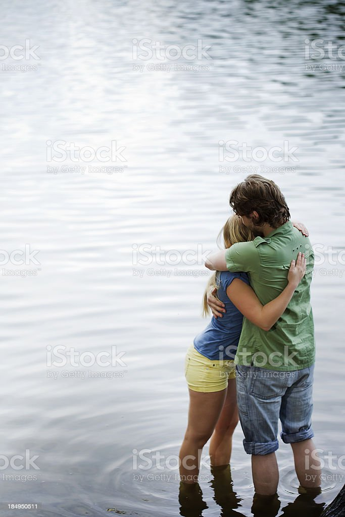 Young Couple Hugging while Standing on Lake Shore royalty-free stock photo