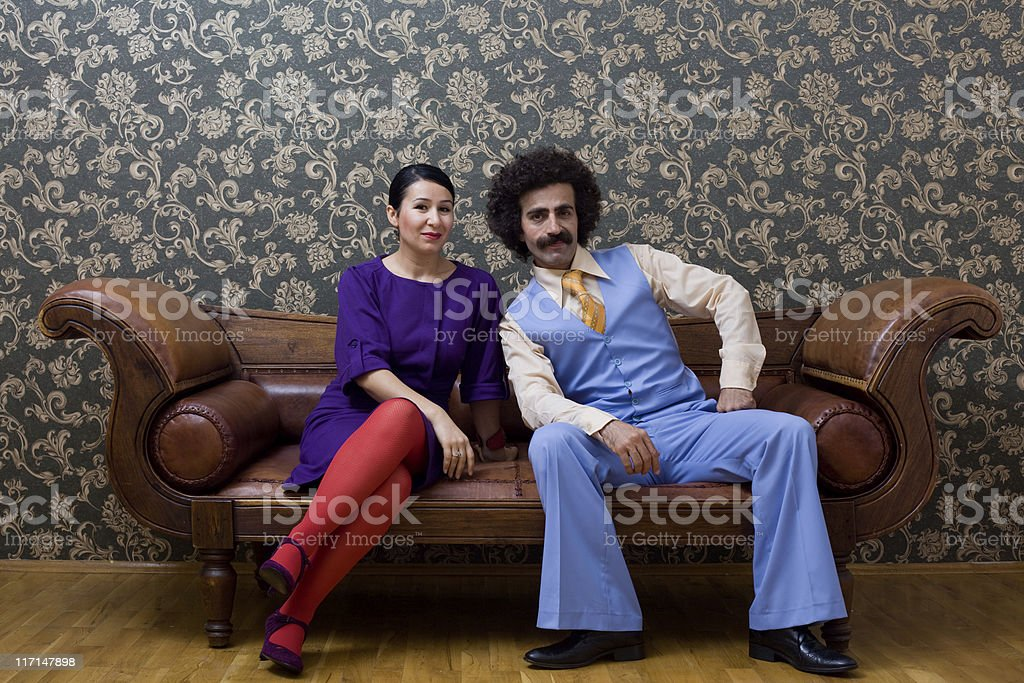 Young couple in 1970s style clothings sitting on leather sofa stock photo