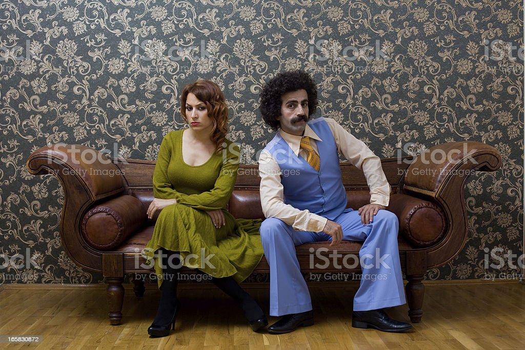 Young couple in 1970s style sitting on sofa royalty-free stock photo