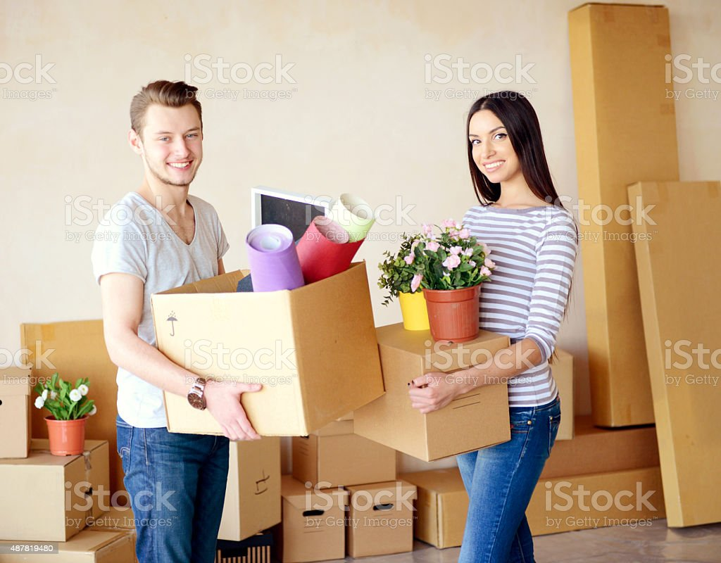 young couple in a new apartment with boxes for moving stock photo