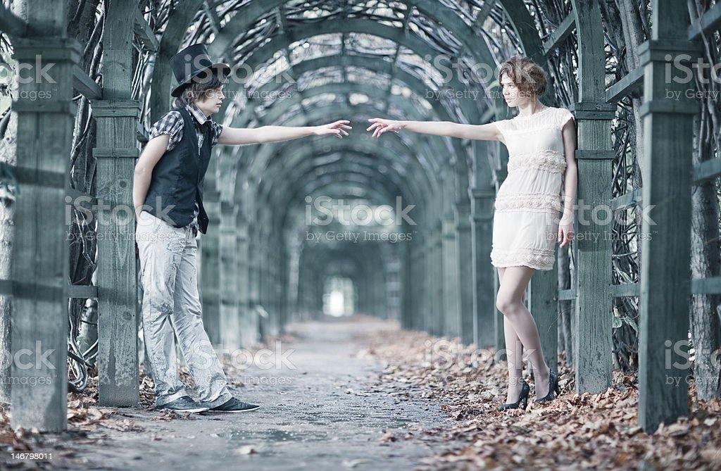 Young couple in a park stretching hands. royalty-free stock photo